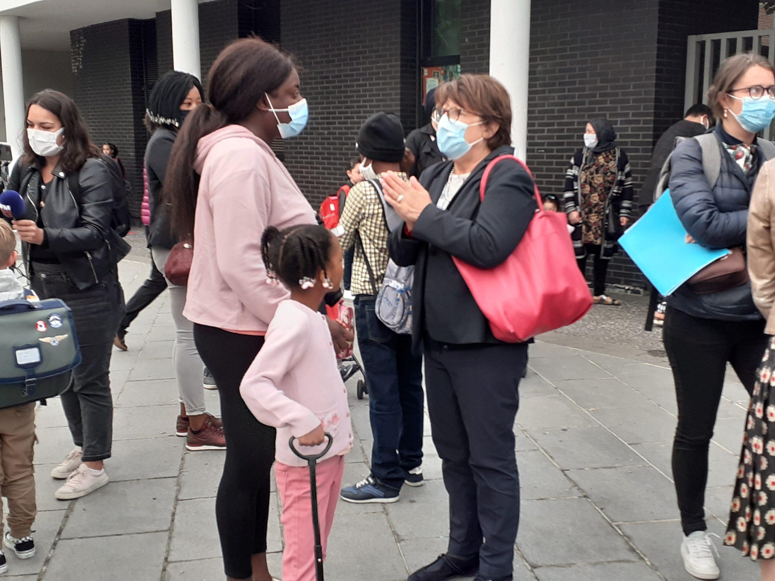 Martine AUbry parle avec un parent d'élève pour la rentrée scolaire