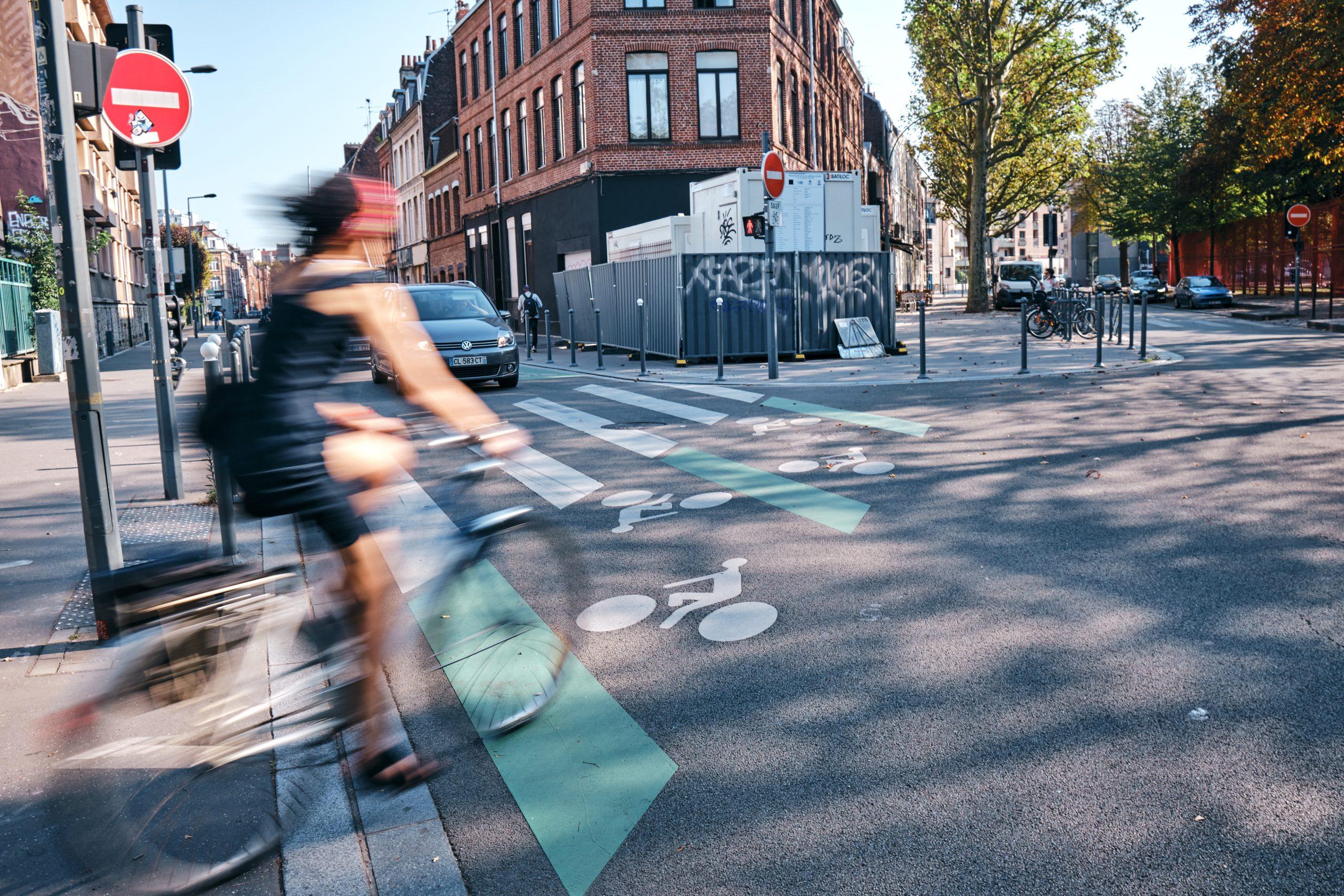 une cycliste traverse une route